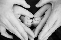 Hände bilden ein Herz um Füße Stockbilder