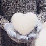 Hände in den gestrickten Handschuhen, die weißes Herz halten Lizenzfreies Stockbild