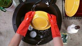 Hände in den roten Gummihandschuhen, die eine gelbe Platte an der Wanne waschen stock footage