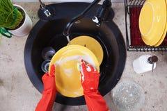 Hände in den roten Gummihandschuhen, welche die Teller waschen Lizenzfreie Stockbilder