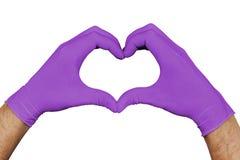Hände in den violetten medizinischen Handschuhen, die das Herzzeichen lokalisiert auf weißem Hintergrund zeigen stockfoto