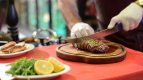 Hände in den weißen Handschuhen schnitten Fleisch auf hölzernem Küchenbrett stock video