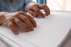 Hände der älteren Frau Blindenschrift im Pflegeheim lesend Lizenzfreies Stockfoto
