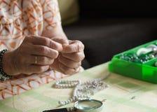 Hände der älteren Frau eine Halskette machend Stockfotografie