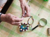 Hände der älteren Frau eine Halskette machend Lizenzfreie Stockbilder