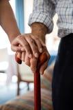 Hände der Ärztin und des älteren Mannes, die gehenden Stock im Ruhesitz halten Stockbild