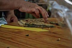 Hände der alten Frau, die Mahlzeit vorbereitend, Straßenphotographie Stockfoto