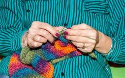 Hände der alten Frau Stricknadeln und multi farbige Wolle für woolwork der warmen Strickjacke für die kalten Wintertage nah herau stockfotos