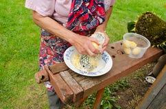Hände der alten Frau zerreiben Schalenkartoffel-Stahlreißwolf Lizenzfreie Stockfotos