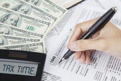 Hände der Arbeitskraft schreibt auf ein Steuerformular stockfotos