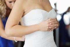 Hände der Braut beim Setzen des Hochzeitskleides Stockbilder