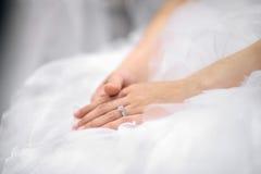 Hände der Braut, die auf Hochzeitskleid legen Stockfoto