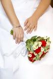 Hände der Braut Hochzeitsblumenstrauß von roten und weißen Blumen halten Lizenzfreie Stockfotos