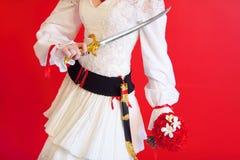 Hände der Braut mit Dolch und Blumenstrauß Lizenzfreie Stockfotos