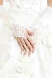 Hände der Braut mit Maniküre in den weißen Spitzehandschuhen lizenzfreie stockfotografie