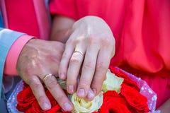 Hände der Braut und des Bräutigams auf dem Hochzeitsblumenstrauß Lizenzfreie Stockbilder