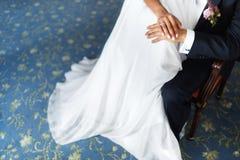 Hände der Braut und des Bräutigams auf dem Kleid Stockbild