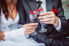 Hände der Braut und des Bräutigams klirren Gläser mit Champagner Lizenzfreie Stockfotografie