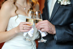 Hände der Braut und des Bräutigams mit Gläsern Lizenzfreie Stockfotografie
