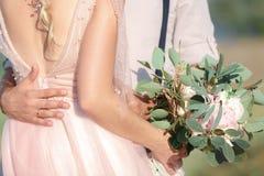Hände der Braut und des Bräutigams mit Hochzeitsblumenstrauß lizenzfreie stockfotos