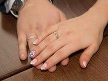 Hände der Braut und des Bräutigams mit Ringen Stockfotos