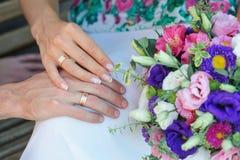 Hände der Braut und des Bräutigams mit Ringen und Hochzeitsblumenstrauß Lizenzfreie Stockfotos