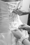 Hände der Brautjungfer Bogen auf Hochzeitskleid binden stockbild
