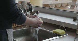 Hände der Frau öffnen Hahn mit kaltem Wasser und waschen gänzlich schönen Apfel, dann setzen ihn in Platte ein Stockfotos