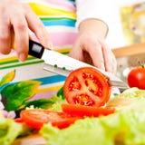 Hände der Frau, die Gemüse schneiden Stockbild