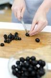 Hände der Frau, die Oliven schneiden Stockbilder