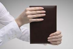 Hände der Frau, die Tagebuch anhalten Lizenzfreies Stockfoto