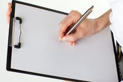 Hände der Frau, die unbelegtes Papier in einem Klemmbrett anhalten Lizenzfreies Stockfoto