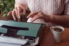 Hände der Frau mit Schreibmaschine und Tasse Kaffee Stockfotografie