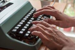 Hände der Frau mit Schreibmaschine und Tasse Kaffee Lizenzfreies Stockfoto