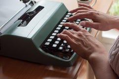 Hände der Frau mit Schreibmaschine und Tasse Kaffee Lizenzfreie Stockfotos