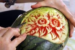 Hände der Frau schnitzten Wassermelone lizenzfreie stockbilder