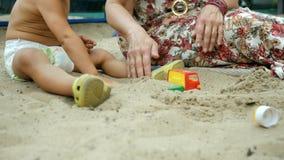 Hände der Frau und des kleinen Kindes, die im Sandkasten sitzen und mit Spielwaren spielen Konzept der Mutterschaft und der Kinde stock footage