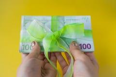 Hände der Frau zwei, die einen Satz von hundert Eurobanknoten mit grünem Bogenknoten, Geschenk oder Dividenden Konzept, Geld der  lizenzfreie stockfotografie