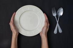 Hände der Frau zwei halten einen der Gabel und weißen Teller des Löffels und auf schwarzem Ba lizenzfreie stockbilder