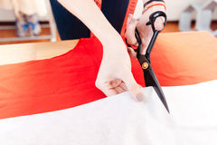 Hände der Frauennäherin, die Scheren verwendet und weißes Gewebe schneidet Stockfoto