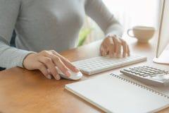 Hände der Geschäftsfrau unter Verwendung der Tastatur und des Computers Asiatin, die an Schreibtisch mit Taschenrechner, Buchbank stockbild