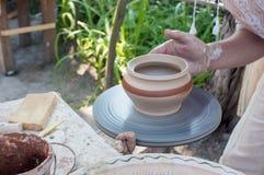 Hände der Herstellung des Tongefäßes auf der Töpferscheibe, ausgewählter Fokus, Nahaufnahme Lizenzfreies Stockfoto