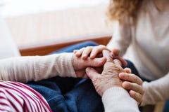 Hände der Jugendlichen und ihrer Großmutter zu Hause lizenzfreie stockbilder