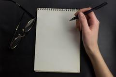 Hände der jungen Frau halten geöffnete Notizbuchseiten mit zensieren im hellen Holztisch mit Bookmarks Stockfoto