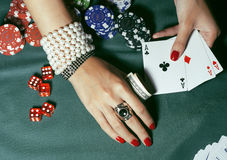 Hände der jungen kaukasischen Frau mit roter Maniküre am Abschluss der grünen Tabelle des Kasinos oben Lizenzfreie Stockfotos