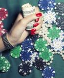 Hände der jungen kaukasischen Frau mit roter Maniküre am Abschluss der grünen Tabelle des Kasinos oben Lizenzfreie Stockfotografie