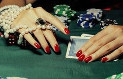 Hände der jungen kaukasischen Frau mit roter Maniküre am Abschluss der grünen Tabelle des Kasinos oben Stockfotografie