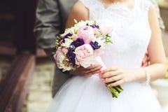 Hände der Jungvermählten mit einem Blumenstrauß der Brautnahaufnahme selektiver Fokus Stockbild