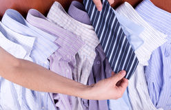Hände der Männer halten die Gleichheit über Hemden an Lizenzfreies Stockfoto