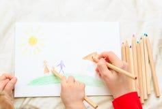 Hände der Mutter und des Sohns, die zusammen zeichnen Stockfotos